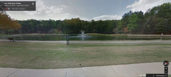 Lake on property with fountain